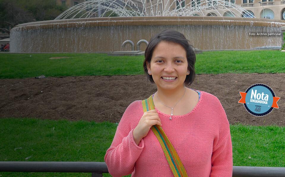 Estudiante mujer, vestida con saco y bolso terciado sonriendo