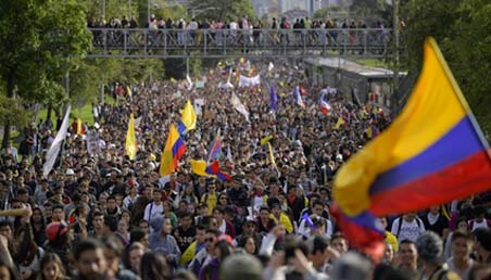 Personas marchando y a un lado la bandera de Colombia.