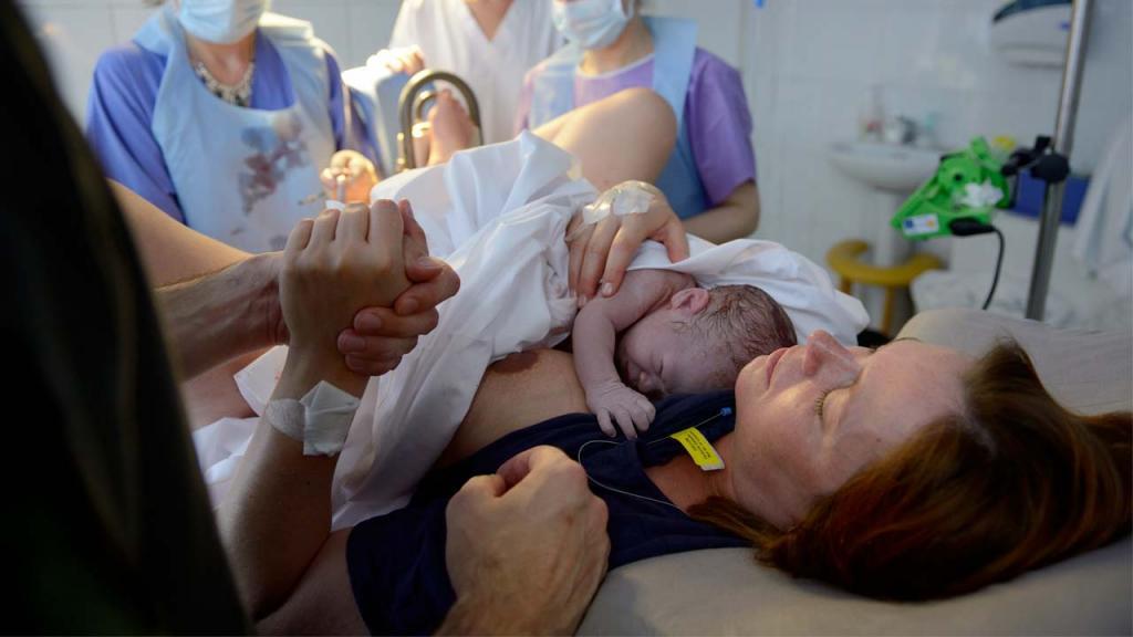 Mujer en un parto, cargando a su bebé.