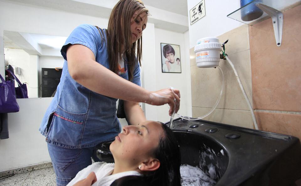 una mujer lava el pelo de una cliente en una peluquería