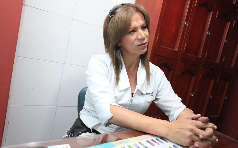 una persona transexual sentada en su oficina
