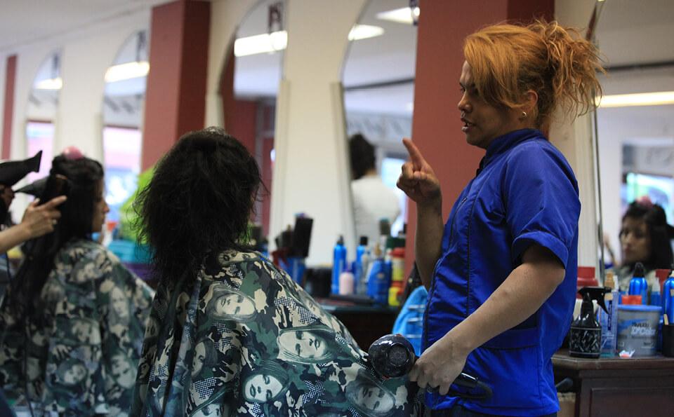 una persona transexual atendiendo a una cliente en una peluquería