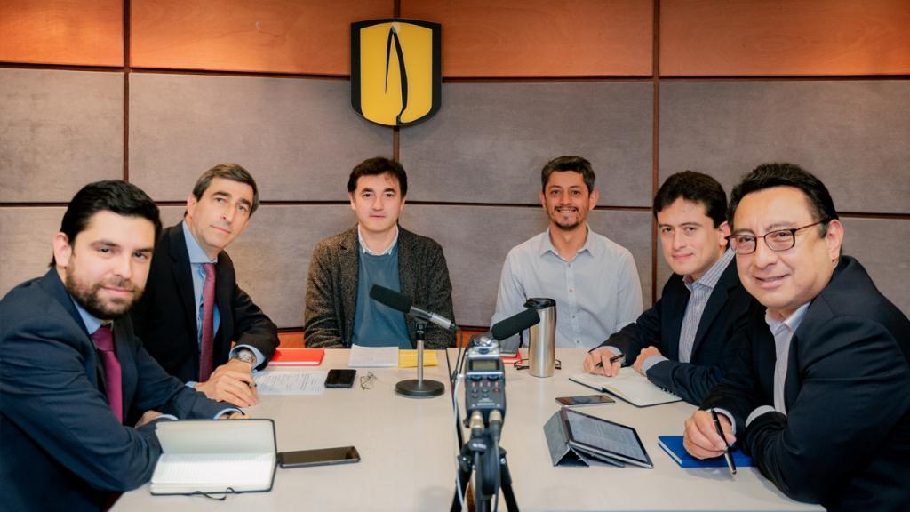 Seis hombres sentados alrededor de una mesa