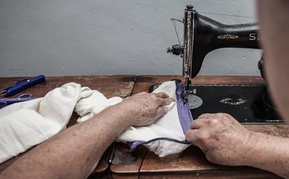 Manos de una anciana sobre una máquina de coser