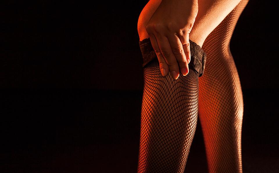 fondo negro, vemos las piernas de una mujer subiendo unas medias de malla