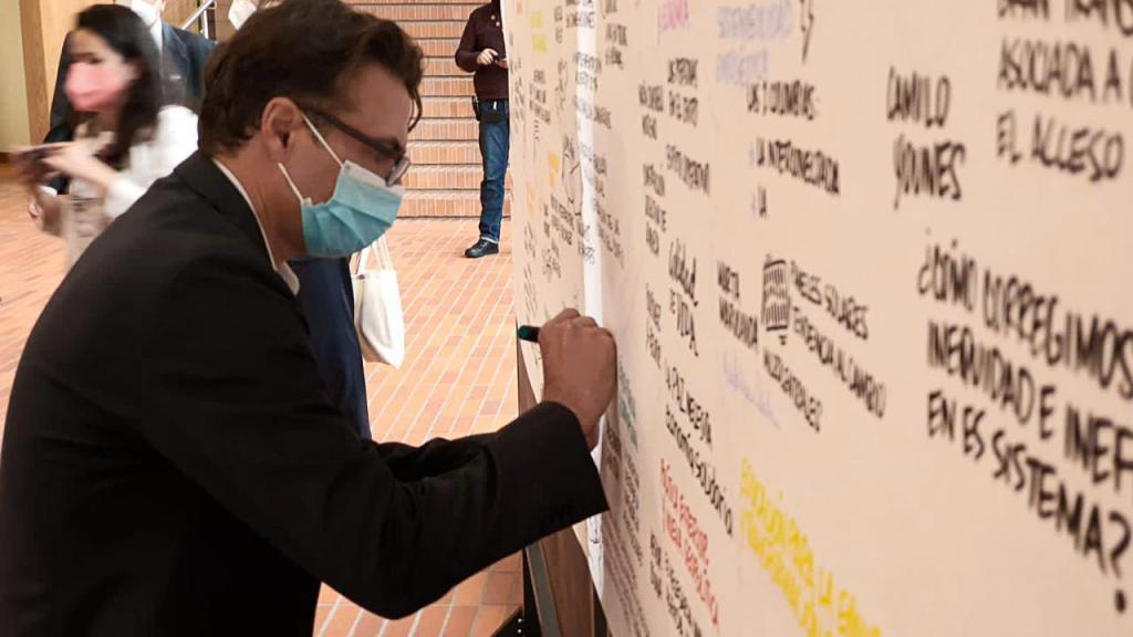Alejandro Gaviria escribiendo en tablero de acrílico