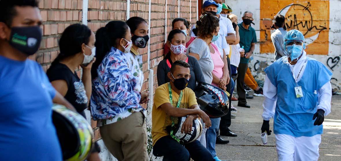Personas hacen fila, mientras un funcionario de salud camina a un lado.