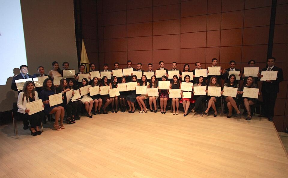 grupo de graduados en un auditorio se acomodan en media luna y exhiben sus diplomas