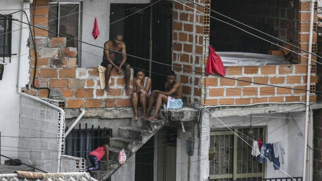 Hombres y mujeres asomados en las ventanas y puertas de sus casas.