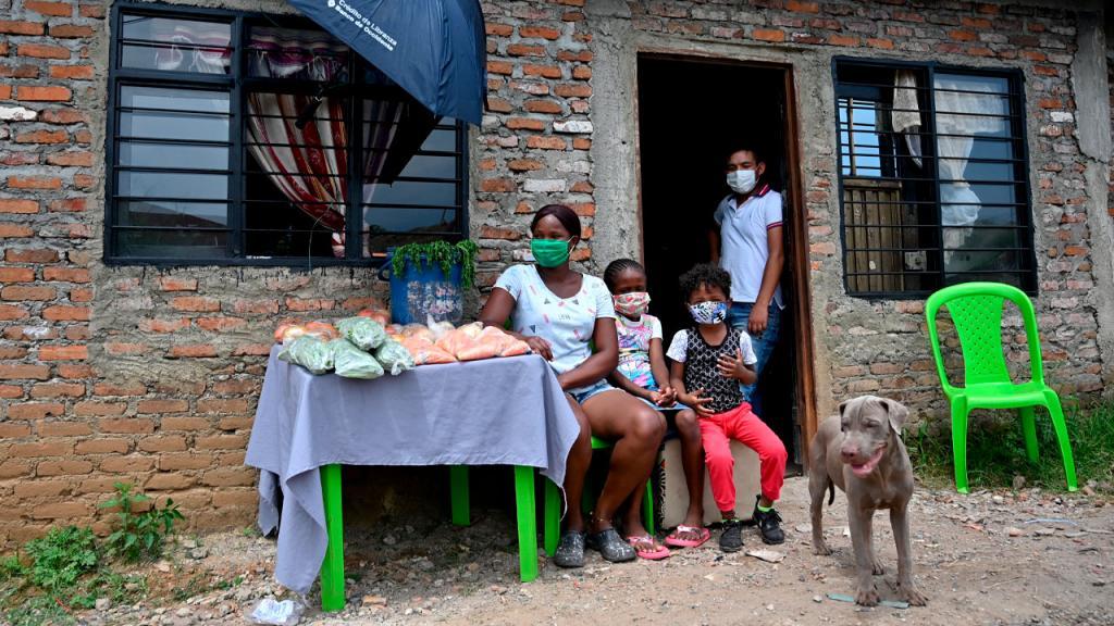 Familia con tapabocas vendiendo verduras en la puerta de la casa