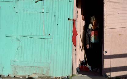 Mujer se asoma por la puerta de una casa.