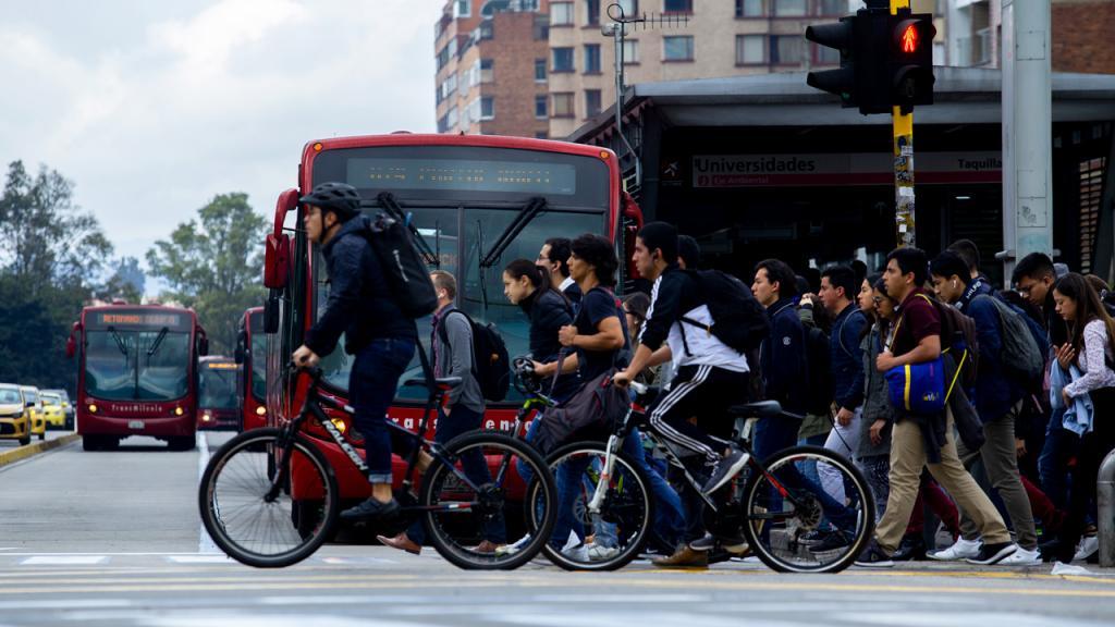 Ciclistas y peatones cruzando una avenida en Bogotá.