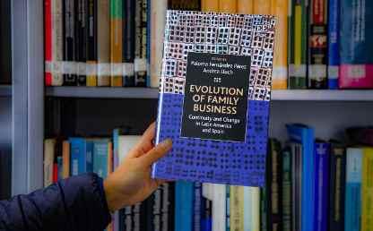 Imagen del libro publicado por Andrea Lluch, sostenido frente a una biblioteca
