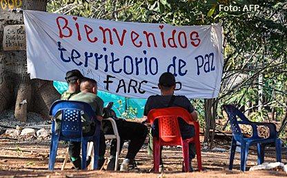 De espaldas, guerrilleros de las Farc sentados frente a una pancarta que dice 'Bienvenidos. Territorio de paz Farc-Ep'.