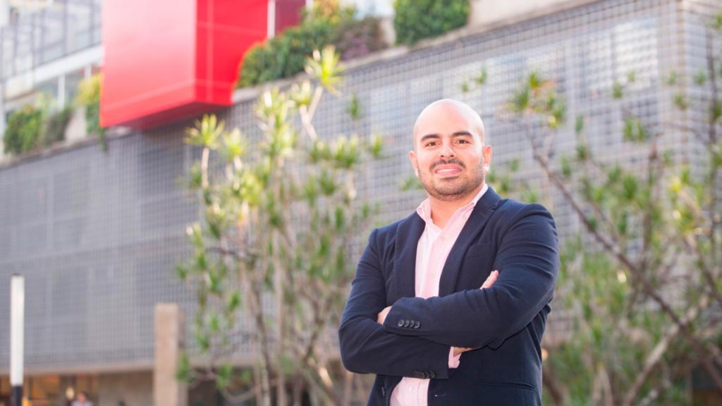 Santiago Tobón frente a un edificio Gris con muro rojo