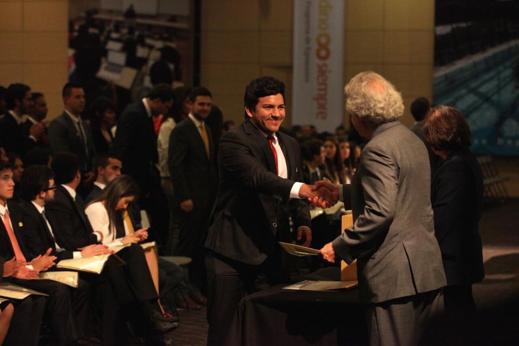 joven de traje recibe diploma de hombre canoso