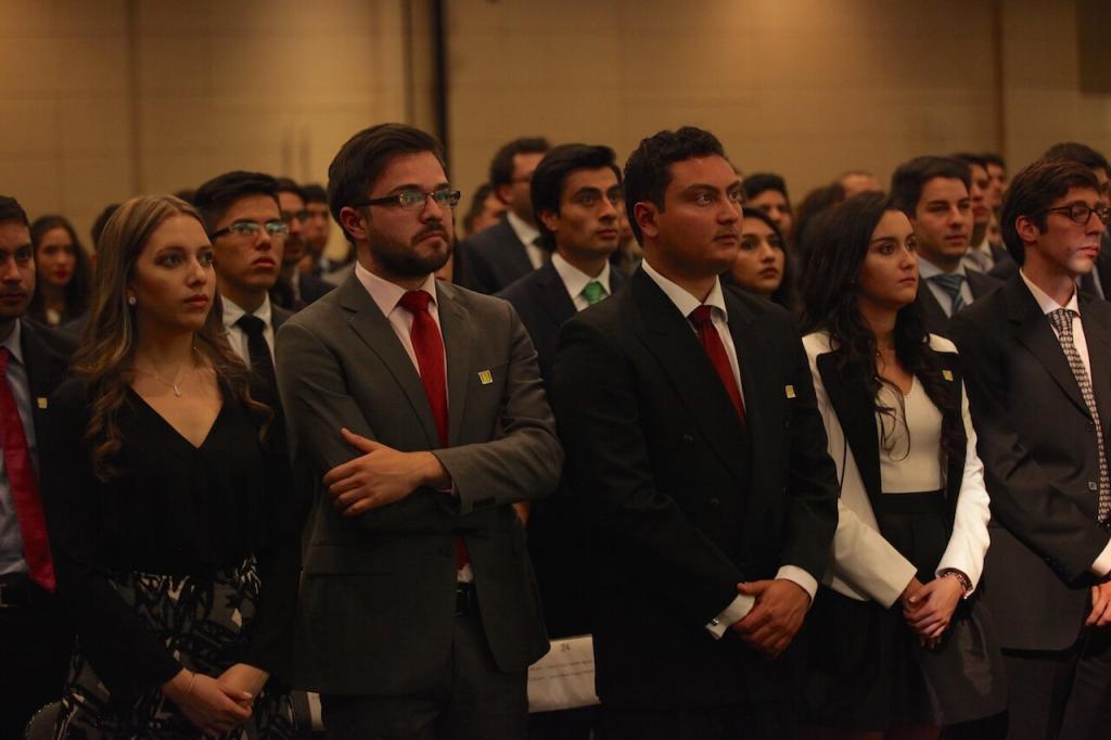 jóvenes en un auditorio de pie en una ceremonia