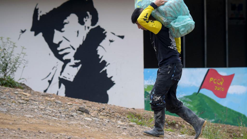 Hombre caminando por una calle destapada y cargando un paquete muy pesado.