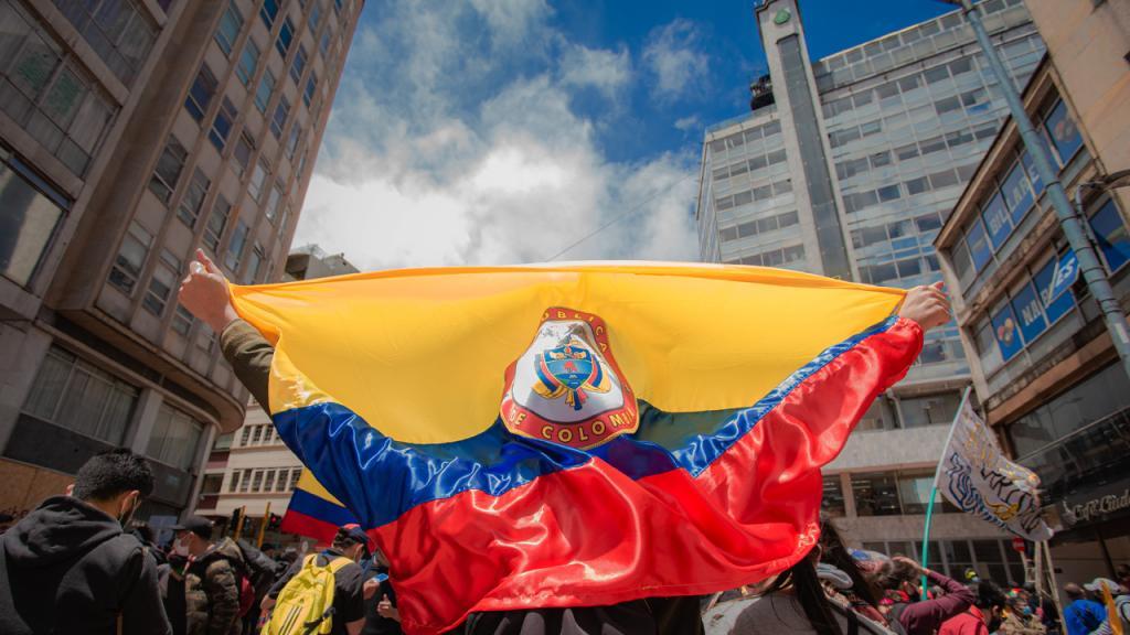 Un manifestante se arropa con la bandera de Colombia.