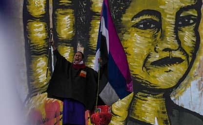 Hombre indígena misak grita, mientras sostiene una bandera.