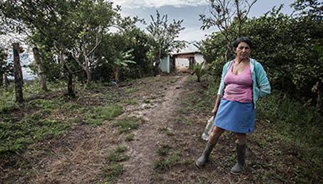 Retrato de una señora del campo parada frente a su casa