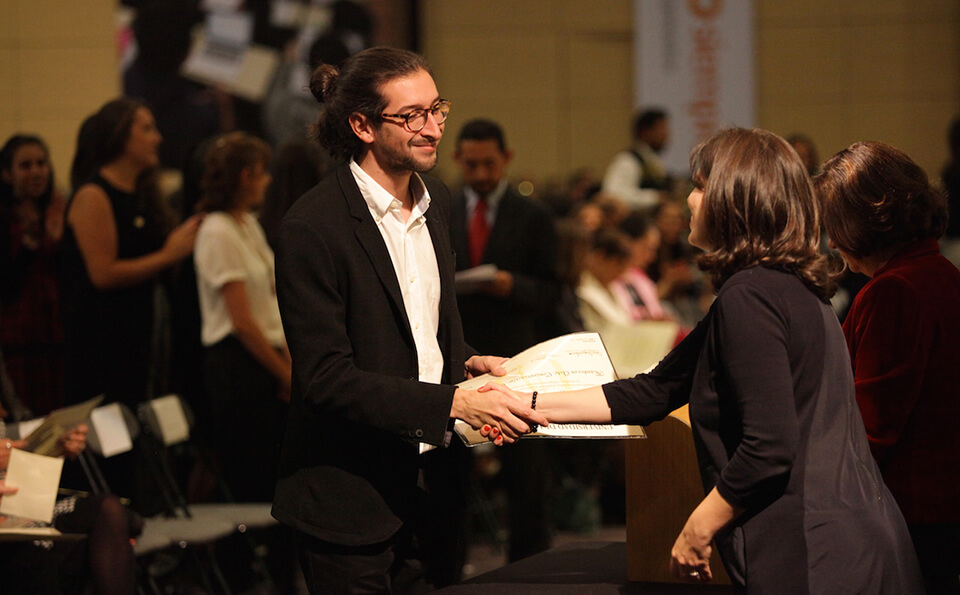 joven de pelo crespo y gafas recibe diploma de grado