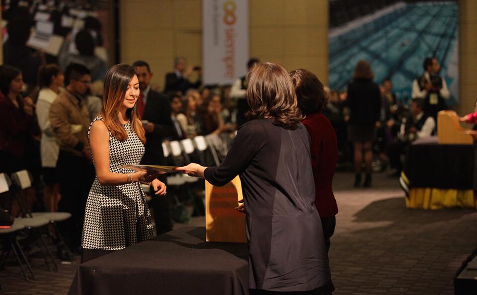 mujer de vestido blanco con negro recibe diploma de grado de manos de dos mujeres