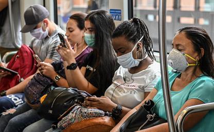 Personas sentadas en el transporte público usando un tapabocas.