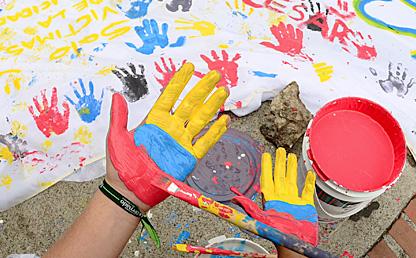 Manos pintadas de color amarillo, azul y rojo, con banderas de paz.