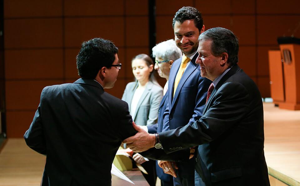 Foto rector entregando diplomas posgrado 2016-1