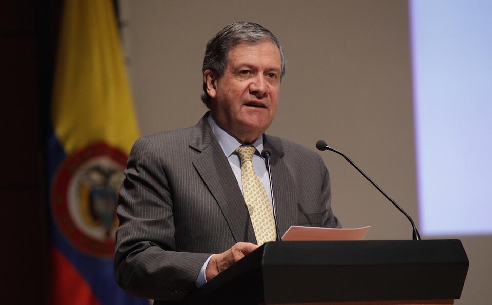 hombre mayor con traje de rayas y corbata amarilla está de pie junto a un atril dando un discurso