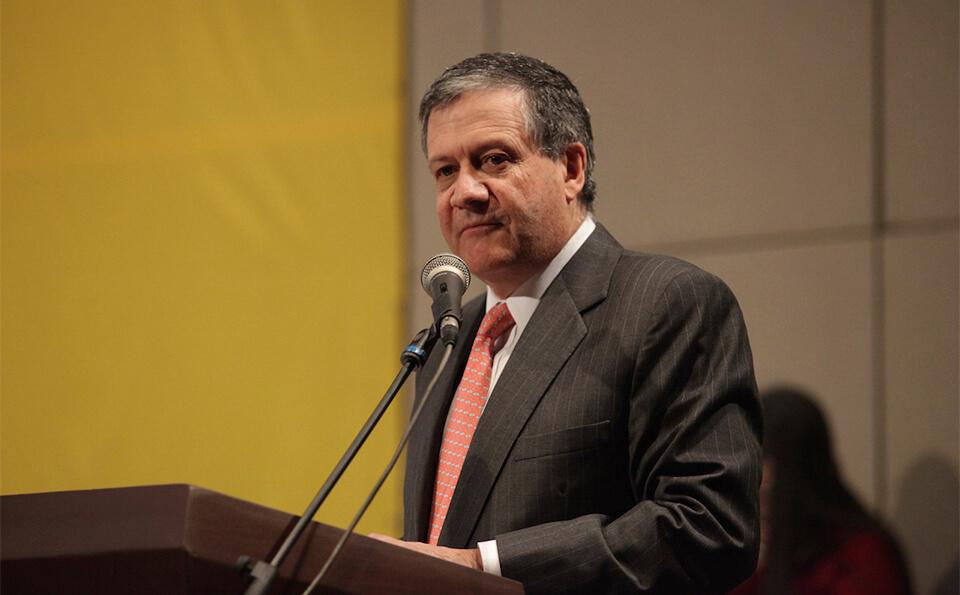 hombre mayor vestido con traje y corbata rosa habla frente a micrófono