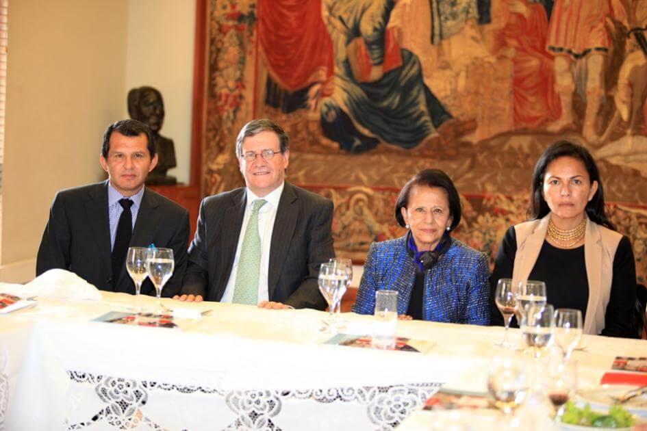cuatro personas sentadas en una mesa, los hombres visten traje con saco y corbata, las mujeres tienen vestido