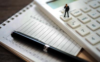 Un esfero y una calculadora sobre un cuaderno.