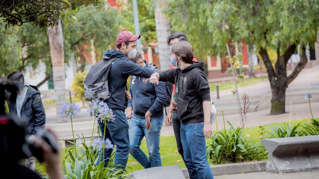 Dos estudiantes se saludan de codo.