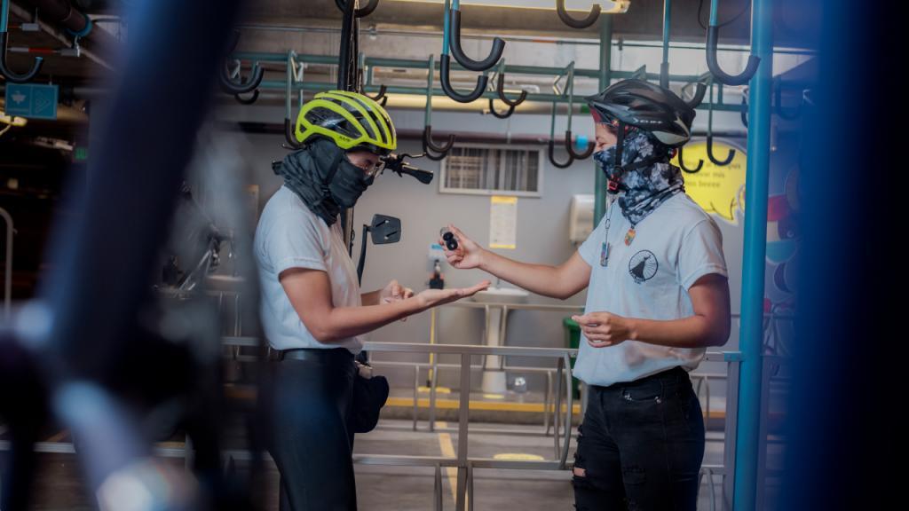 Estudiantes desinfectándose después de llegar en bicicleta