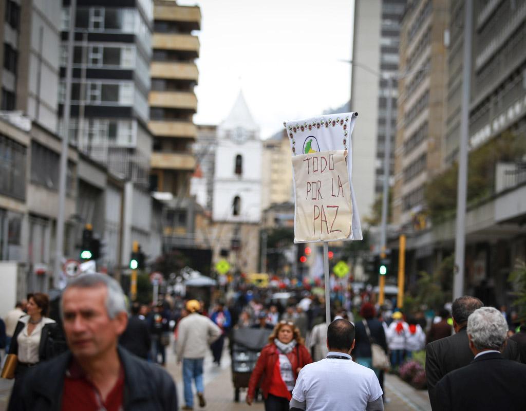 Peatones en las calles del centro de Bogotá. Una de ellas levanta un pequeño cartel que dice: 'Todo por la paz'.