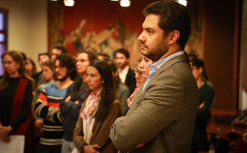 hombre cruzado de brazos en medio de discurso de evento