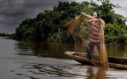 Pescador sostiene malla en una canoa sobre el mar