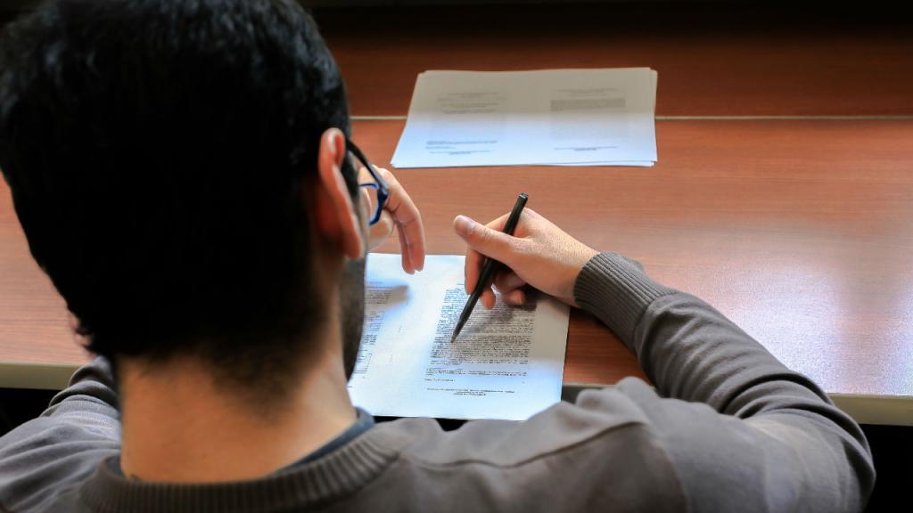 Un joven estudiante escribiendo sobre un papel.