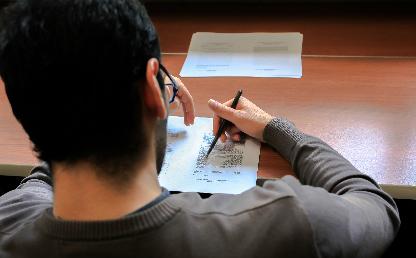 Un joven estudiante escribendo sobre un papel.
