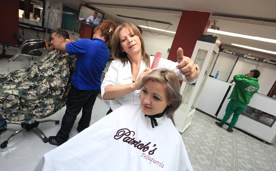 una peluquera peina a una mujer, vemos al fondo un peluquero atendiendo a un cliente