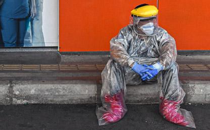 Hombre médico sentado en un andén, con elementos de bioseguridad Eduardo Behrentz