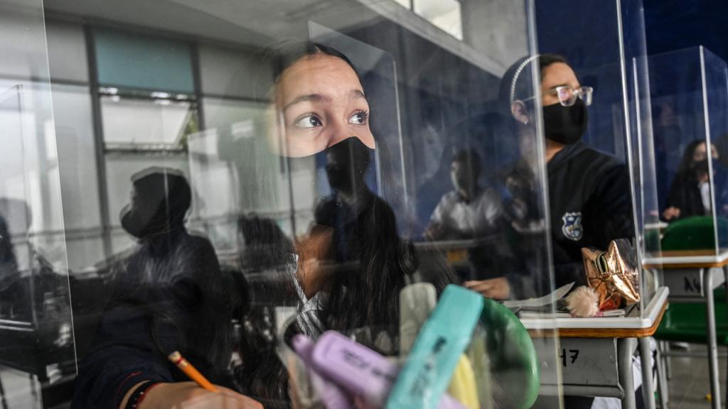 Niños en aula mirando por la ventana y utilizando tapabocas