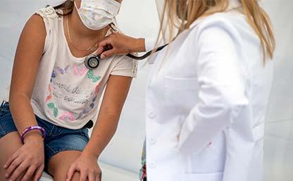 Foto de doctora examinando una paciente con un estetoscopio