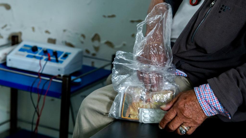 Una mano de un anciano sostiene una bolsa plástica con medicamentos.