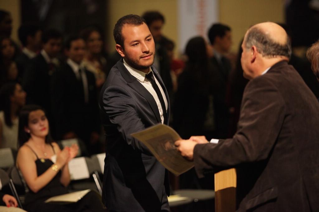 joven de traje gris y corbata negra recibe diploma de grado