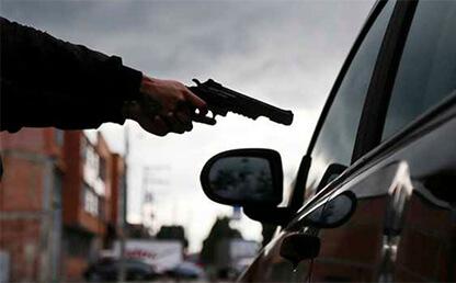 Persona con pistola apunta a un automóvil
