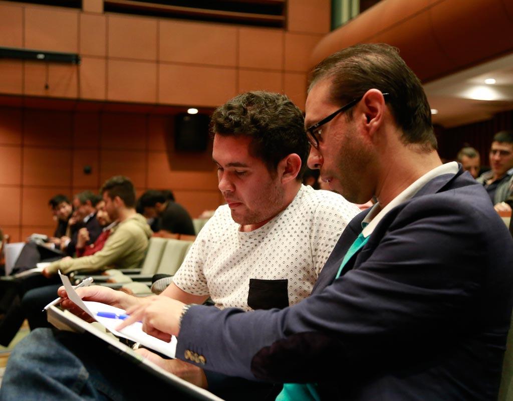 Dos personas en un auditorio revisan un cuaderno.