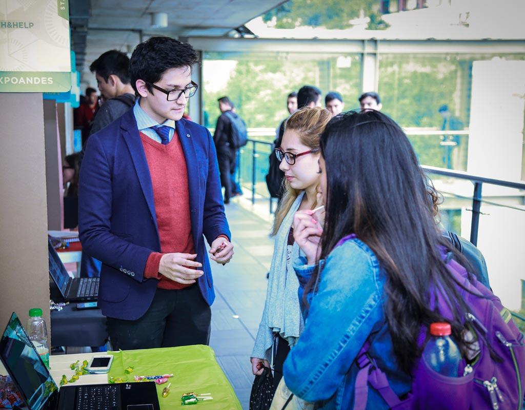 Estudiantes en un stand exponen sus trabajos